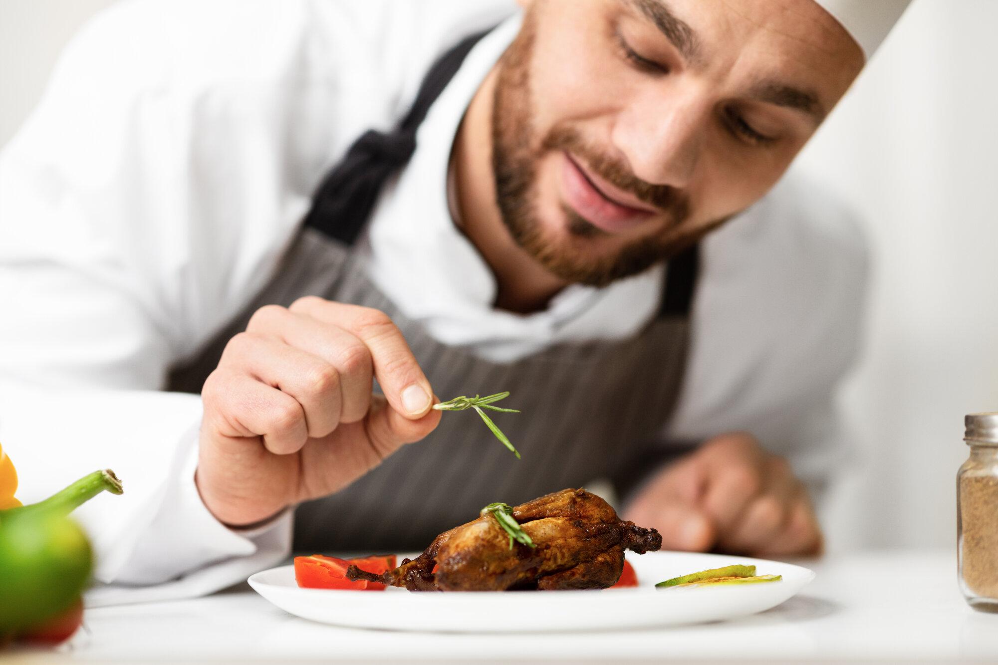 cook man decorating chicken dish preparing dinner LJEUG98 - Startseite