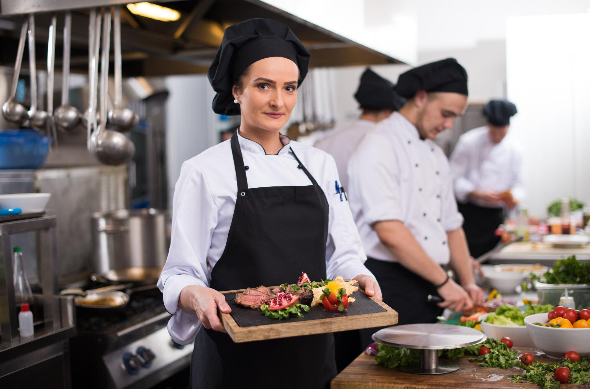 female chef holding beef steak plate PTHM3QD - Startseite
